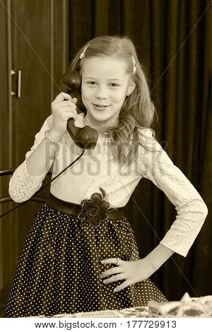 Cheerful little girl talking on a vintage telephone in the interior of the sixties of the last century.Black-and-white photo. Retro style.