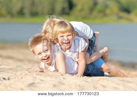 Portrait Of Three Children Playing On The Beach