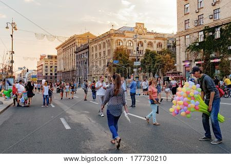 Kiev, Ukraine - September 11, 2016: Khreshatyk Street at weekend in Kiev. People walking through the street passing cafes restaurants and shops. The seller of colored balloons in the foreground