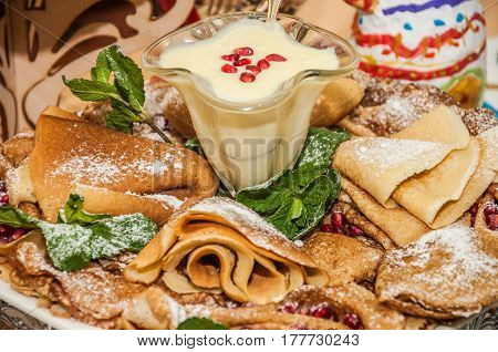 Pancakes with condensed milk and decorated with pomegranate grains and aromatic mint during the celebration Russian Shrovetide (pancake week)