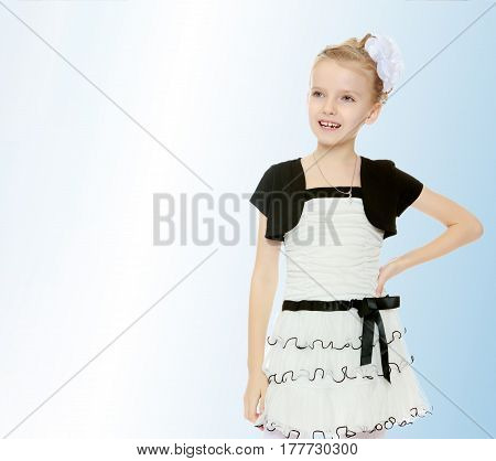 Beautiful little blonde girl dressed in a white short dress with black sleeves and a black belt.Girl poses for the camera.On the pale blue background.