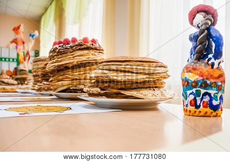 A stacks of pancakes and folk toy during the celebration Russian Shrovetide (pancake week)