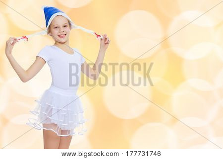 Cheerful little girl gymnast in white sport dress in a cap of Santa Claus.Brown festive, Christmas background with white snowflakes, circles.
