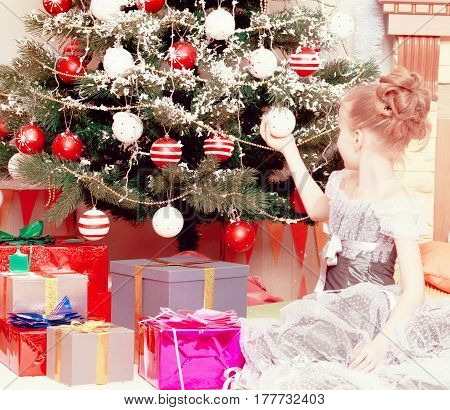 Beautiful little girl in a dress of Princess around the Christmas tree.She sits on the floor beside the gifts and decorates the Christmas tree. Close-up.Creative toning of a photograph.