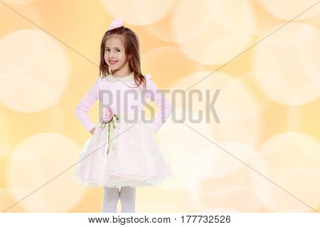 Dressy little girl long blonde hair, beautiful pink dress and a rose in her hair.She put hands on hips.Brown festive, Christmas background with white snowflakes, circles.
