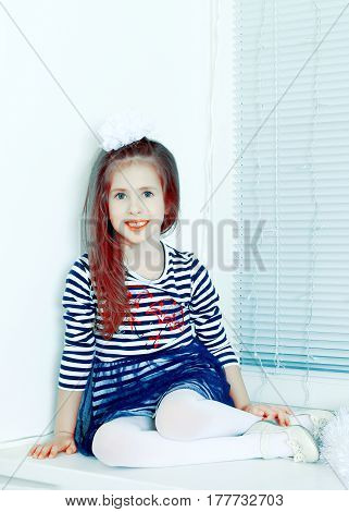 Little girl in blue striped dress and a white bow on her head.She sits at the window and looking straight to the camera.Creative toning of a photograph.