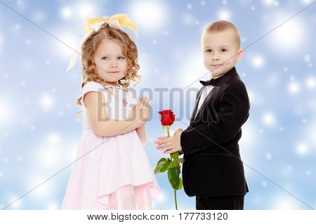 Little boy in black suit with bow tie gives a big red rose charming little girl.Blue Christmas festive background with white snowflakes.