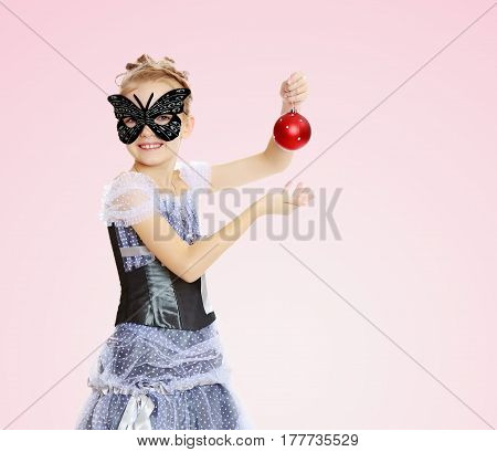 Slender little girl , with beautiful hair on his head, elegant long Princess dress.Posing in carnival mask.She admires the beautiful Christmas decorations.Pale pink gradient background.