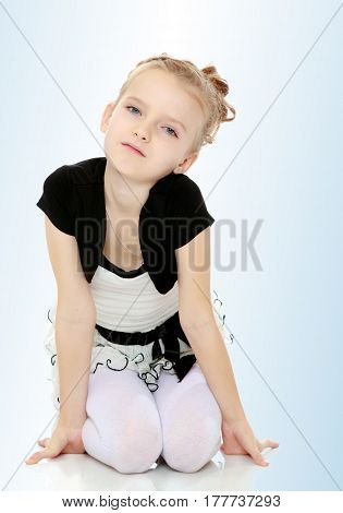 Beautiful little blonde girl dressed in a white short dress with black sleeves and a black belt.Girl sitting on the floor leaning on hands and smiling at the camera.On the pale blue background.