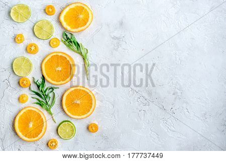 colorful sliced citrus with oranges and lime on gray stone table background top view mock up