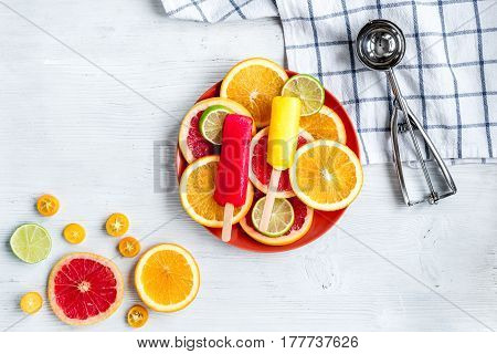 homemade ice-cream with sliced oranges and lime on stone table background top view mockup