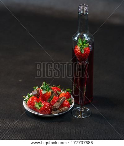 Liqueur In Bottle And  In Glass With Strawberries, Strawberries With Pieces Of Chocolate On A White