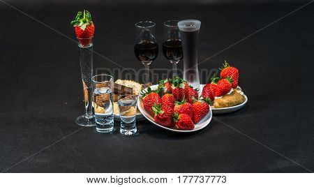 Liqueur  And Vodka In Glasses, Strawberries And Cookies With Pieces Of Chocolate On A White Saucers