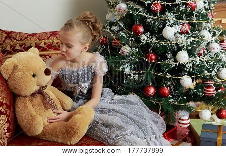 Beautiful little girl in a dress of Princess around the Christmas tree.She sits on the couch in the bell of Santa Claus, and hugging a big Teddy bear.