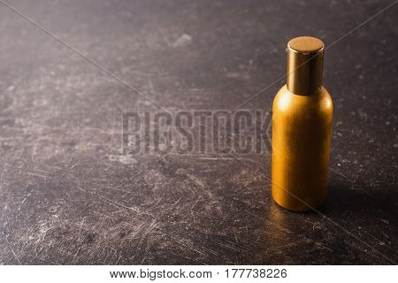 A golden bottle with perfume on a dark marble background. golden bottle concept. The bottle is on the table