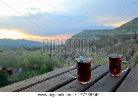 Travel To Cappadocia, Turkey. The Couple Of Turkish Tea Cups On A Background Of A Sunset In The Moun
