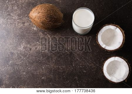 Coconut and coconut milk on a dark marble background. Exotic large walnut. Personal care. Spa treatments. Coconut concept