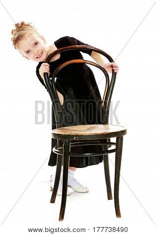The slender little blonde girl dancer in the long dress of black color made specifically for performing .A girl stands near the old Vienna chair and holds his back with his hands.Isolated.