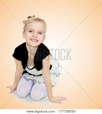 Beautiful little blonde girl dressed in a white short dress with black sleeves and a black belt.The girl kneeling on the floor smiling directly into the camera.