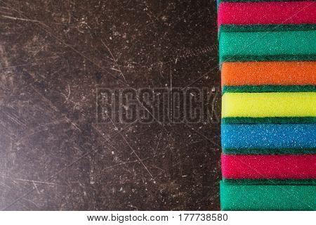 Copyspace sponges. Colored sponges against dark marble background. Items for hygiene and washing dishes. Sponges concept