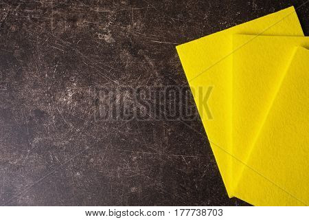 Yellow rag on a dark marble background. Items for hygiene and washing dishes. Rag concept. Flat lay rag. Rag on table