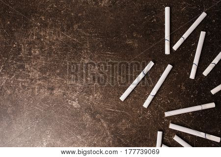 Conceptual picture with a cigarette. Cigarette on a dark marble background. Bad habit. Health care. Cigarette concept