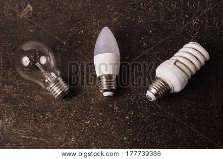LED bulb incandescent lamp fluorescent lamp on a dark marble background. To save energy. Eco lamp concept. Lamp on table