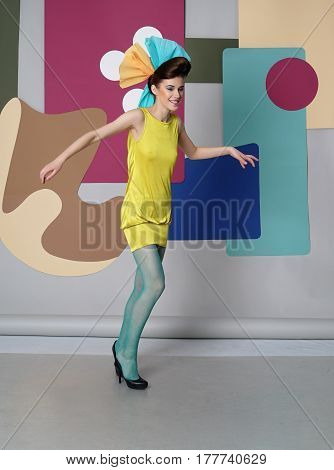Danish design. Woman dressed in short yellow dress, green tights, high heels, hands bent in the elbows. Backdrop: circles, Egg chair.