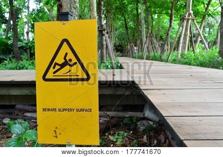 Yellow metal beware slippery surface warning sign at the walkway in the garden