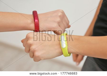 Hands of young women with fitness trackers, closeup