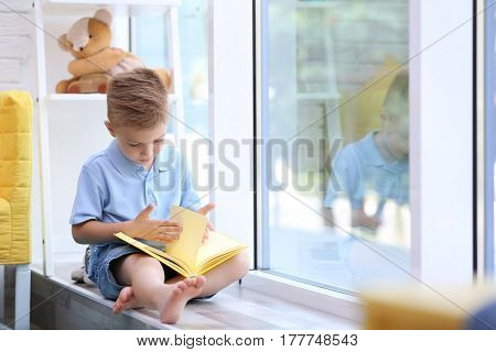 Cute boy reading interesting book on windowsill