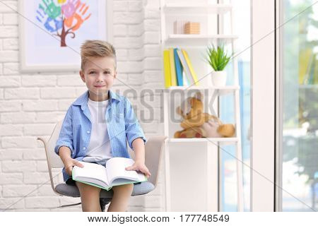 Cute boy sitting on chair and reading book