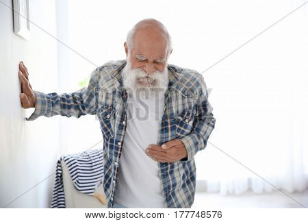 Senior man with pain in tummy holding on to the wall