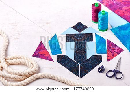 Sewing patchwork of block anchor spools of threads fabrics rope lie on white surface