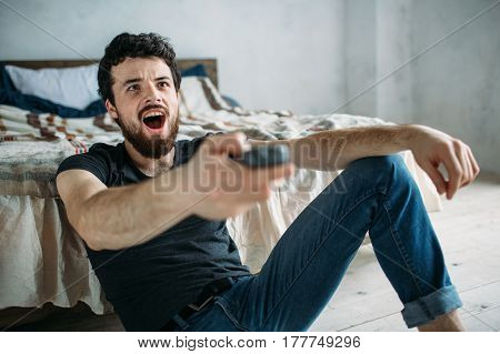 Young Handsome Man Watching Tv On A Floor At Home