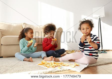 Cute African girls sitting on floor and eating oranges