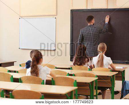 Pupils listening teacher in classroom
