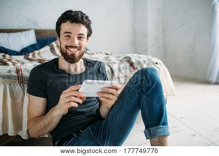 Portrait Of A Happy Young Man Relaxing And Watching A Tv Show On A Tablet Computer