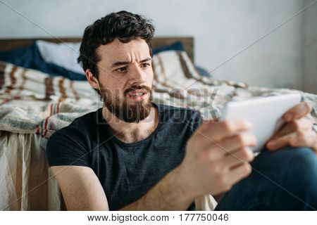 Portrait Of A Young Man Relaxing And Watching A Tv Show On A Tablet Computer