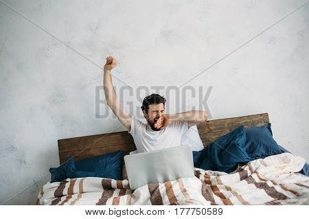 Handsome Man Sitting In Bed And Stretching