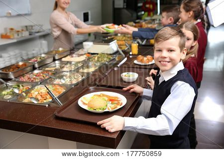 Cute little boy receiving food in school cafeteria