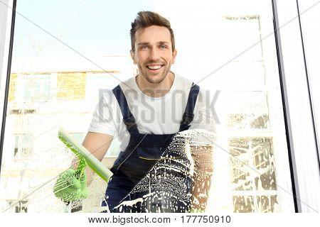 Young man washing window, view through glass