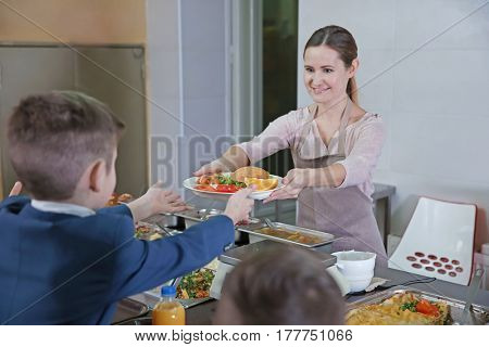 Pleasant woman giving lunch to school boy in cafeteria