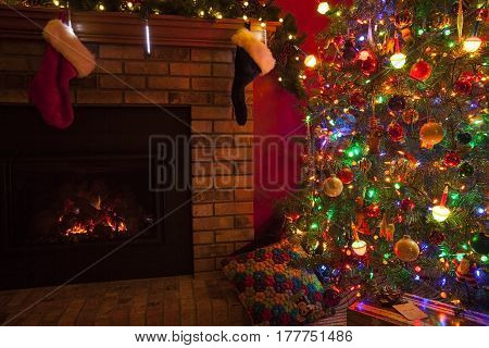 Christmas fireplace with stockings and Christmas tree and gifts.