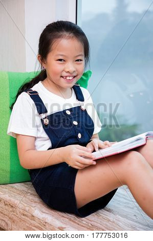 Asian Chinese Little Girl Reading Book On The Windowsill