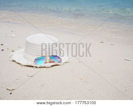 Fashionable mirror glasses and white hat on sand beach background