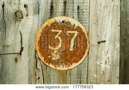 Vintage grunge square metal rusty plate of number of street address with number 37 closeup.