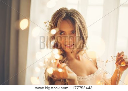 Young lovely housewife with a garland. Girl in sexy gown. Good morning. Playful glance. Soft focus. Toning. Creative bokeh.