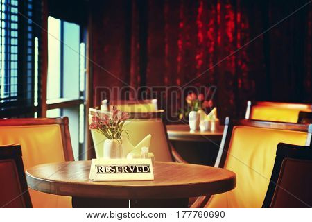 Reserved table close-up. Round wooden coffee table reserved. Relaxation background in warm tones.