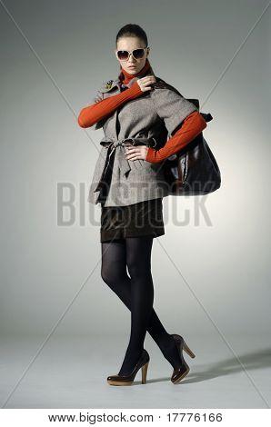 schöne Mode-Modell mit einer Tasche posiert auf hellem Hintergrund